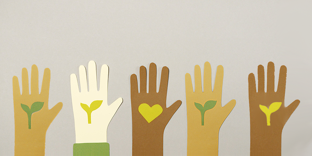 5 hands (made out of small cut out paper) in different shades of skin color: from dark to light hold up five fingers each. The four hands on either side of the frame have a budding leaf in their palms. The hand at the center has a heart in its palm.
