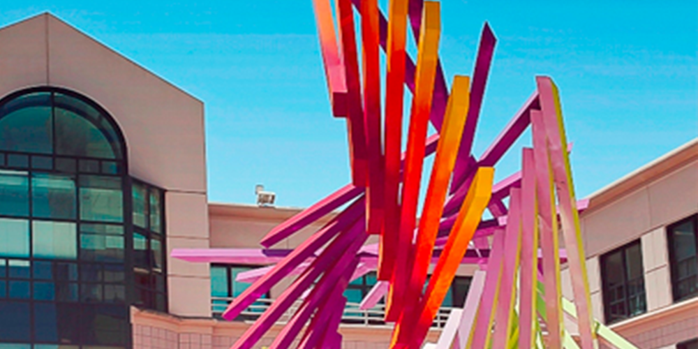 An exterior shot of 500 12th Street scene from the middle of 12 Street City Center. It is a beige building, with arch-shaped windows that reflect the sun. On the right, a yellow, orange and, purple abstract sculpture reaches up to the blue sky.
