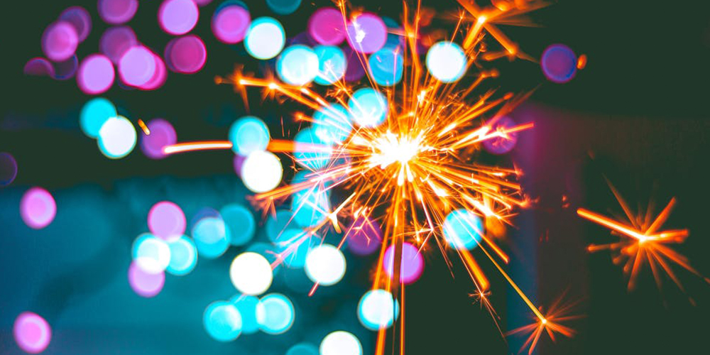A bright, beautiful sparkler lights up the dark with orange embers and flashes of purple and blue light.