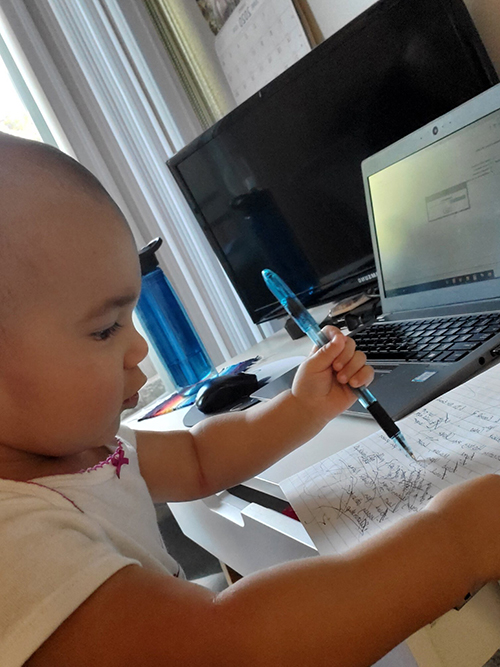 "An adorable 15 month old ""works"" from home sitting at a desk with a pen in her hand."